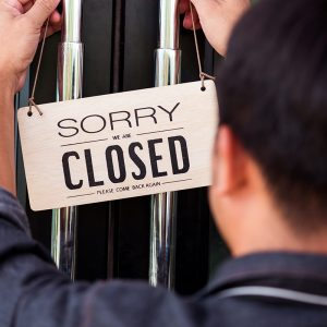 "Man hanging up a ""sorry we are closed"" sign on the door"