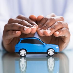 Hands covering blue car